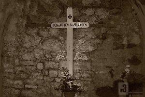 """Gedenkkreuz am """"deutschen Friedhof"""" im Fort Douaumont. Hinter der Mauer liegt der Gang zu den Frontwallkasematten I und II. In diesen wurden über 600 Opfer der Explosionskatastrophe vom 8. Mai 1916 bestattet."""