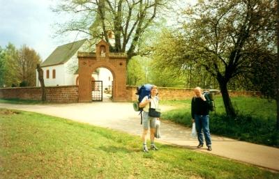 Pilgerreisende vor der ehemaligen Pfarrkirche  St. Johannes  der Täufer auf dem Kasteler Hochplateau. Die Kirche wurde als Gedenkstätte in den anschließenden Ehrenfriedhof der  Gefallenen des zweiten Weltkrieges einbezogen.