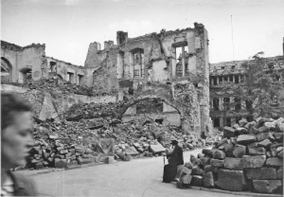 Eines der historischen Fotos in der Ausstellung  zeigt das zerstörte städtische Kaufhaus und im Hintergrund das alte Rathaus auf dem Kornmarkt. Bildnachweis: Wissenschaftliche Bibliothek der Stadt Trier