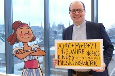 Pfarrer Dirk Bingener, Präsident des Kindermissionswerks 'Die Sternsinger' präsentiert die Sonderbriefmarke zum Jubiläum des Hilfswerks. Bildquelle: © Dominic Winkel / Kindermissionswerk